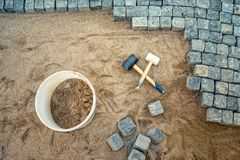 Bouw van bestratingsdetails, keibestrating, steenblokken en rubberhamers op bouwwerf Stock Afbeeldingen