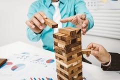 Bouw van de bedrijfsman en vrouweneinde de houten toren voor bouwvallig stock fotografie