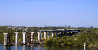 Bouw van de brug en de weg op rivier Stock Foto