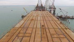 Bouw van de brug De techniekfaciliteiten voor de bouw van een spoorweg en een auto overbruggen over de Straat stock videobeelden