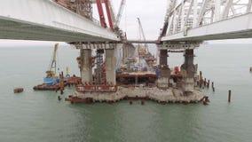 Bouw van de brug De techniekfaciliteiten voor de bouw van een spoorweg en een auto overbruggen over de Straat stock footage