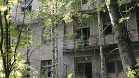 Bouw van de voorgevel de oude vernietigde baksteen met gebroken vensters in industriezone van de verlaten stad Vernietiging of sc stock footage