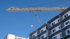 Bouw van een gebouw met meerdere verdiepingen De bouwkraan heft de concrete plak over het dak op stock video