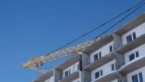 Bouw van een gebouw met meerdere verdiepingen Kranendraaien aan de kant over het dak op hemelachtergrond stock video