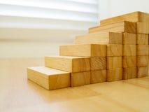 Bouw van houtsnede die als staptrede stapelen op houten vloer Concept de zaken van het de groeisucces Stock Foto's