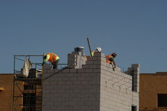 Bouwbemanning die bij de nieuwe bouw werken Stock Fotografie