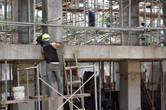 Bouwconstructiemetselaar die het pleisteren het werk doen die zich op steigerpijpen bij het werkplaats bevinden royalty-vrije stock afbeelding