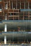 Bouwconstructieplaats met meerdere verdiepingen met arbeiders op steigers stock foto's