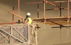 Bouwer aan het bouwwerfwerk aangaande steiger stock foto