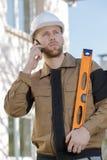 Bouwer bij bouwterrein die op mobiele telefoon spreken Royalty-vrije Stock Afbeeldingen