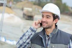 Bouwer in bouwvakkers op telefoon in openlucht Royalty-vrije Stock Fotografie