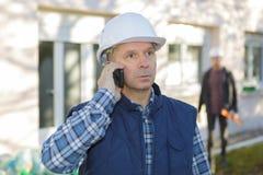 Bouwer die in bouwvakker op mobiele telefoon spreken Royalty-vrije Stock Foto's