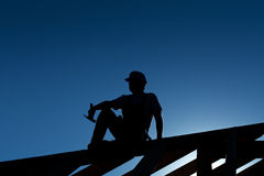 Bouwer die bovenop dakstructuur rust Stock Fotografie