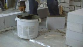 Bouwer die mortier aan kant van gelucht concreet blok met spatel zetten stock video