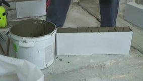 Bouwer die mortier aan kanten van gelucht concreet blok met spatel zet stock videobeelden