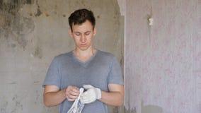 Bouwer die op handschoenen zetten stock video