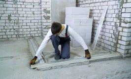 Bouwer die tekens bij de concrete stichting met de heerser van de bouwheerser doen royalty-vrije stock afbeeldingen