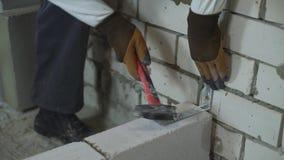 Bouwer het hameren toetredende klem aan verticale bakstenen muur stock videobeelden