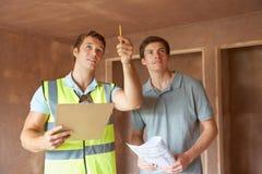 Bouwer And Inspector Looking bij Nieuw Bezit stock afbeelding