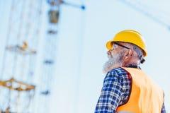 Bouwer in weerspiegelend vest en bouwvakker die zich bij bouwwerf bevinden, stock afbeelding