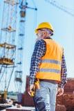 Bouwer in weerspiegelend vest en bouwvakker die zich bij bouwwerf bevinden, royalty-vrije stock foto's