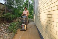 Bouwers aanstampend zand rond het huis bij de bouwwerf royalty-vrije stock foto's