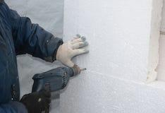 Bouwers boormuur voor het installeren van ankers om de stijve raad van het isolatieschuim te houden stock foto's