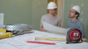 Bouwers die bouwdocumentatie bestuderen alvorens reparatie in gebouw te beginnen stock footage