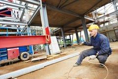 Bouwersarbeider bij bouwwerf Stock Foto