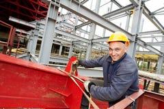 Bouwersarbeider bij bouwwerf Stock Afbeeldingen