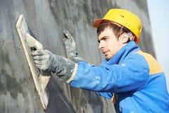 Bouwersarbeider bij het pleisteren van het voorgevelwerk royalty-vrije stock foto