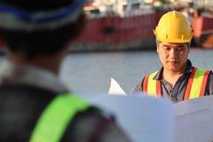 Bouwersarbeider in eenvormig met veiligheidsgordel bij bouwwerf royalty-vrije stock afbeeldingen