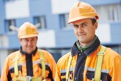 Bouwersarbeiders bij bouwwerf Stock Afbeeldingen