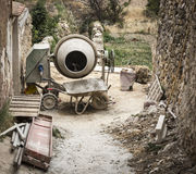 Bouwhulpmiddelen - een elektrische cementmixer een kruiwagen en steigers Stock Foto's