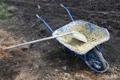 Bouwhulpmiddelen - een schop en de kar op wielen met zand stock foto's