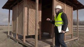 Bouwingenieur die de houten bouw controleren stock footage