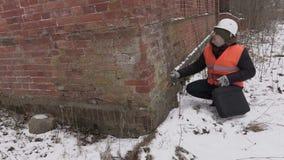Bouwinspecteur die bakstenen controleren bij de oude bouw stock footage