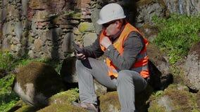 Bouwinspecteur die dichtbij oude muur denken stock videobeelden