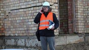 Bouwinspecteur die met documenten het gebouw controleren stock video