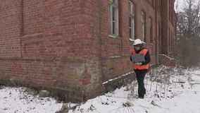 Bouwinspecteur die met laptop de oude bouw controleren stock footage