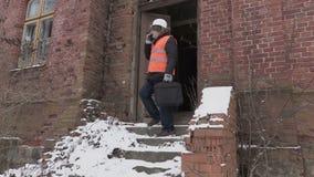 Bouwinspecteur die op celtelefoon dichtbij de oude bouw spreken stock footage