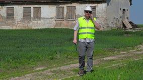 Bouwinspecteur die op slimme telefoon dichtbij oud verlaten, beschadigd huis op grasgebied spreken stock videobeelden