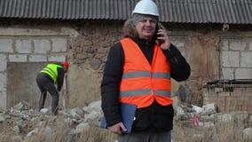 Bouwinspecteur die op smartphone in arbeider die als achtergrond spreken voorhamer met behulp van stock videobeelden
