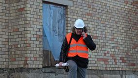 Bouwinspecteur die op smartphone dichtbij het gebouw spreken stock footage