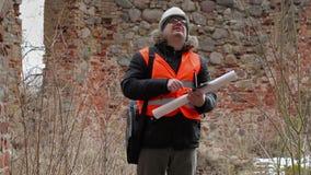 Bouwinspecteur die tabletpc met behulp van bij oude ruïnes stock footage