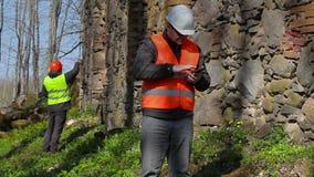 Bouwinspecteur die tabletpc met behulp van dichtbij oude muur vóór restauratie stock video