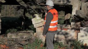 Bouwinspecteur met de smartphone dichtbij verlaten beschadigde bouw stock videobeelden