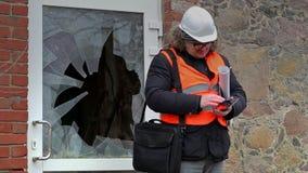 Bouwinspecteur met het gebroken venster van tabletpc dichtbij stock videobeelden
