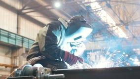 Bouwinstallatie Een mensenarbeider in een helm die een lassenmachine op metaaldetail met behulp van Brandfonkelingen stock footage