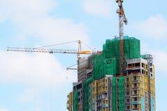 Bouwkraan en de bouw in aanbouw tegen blauwe hemel Stock Foto